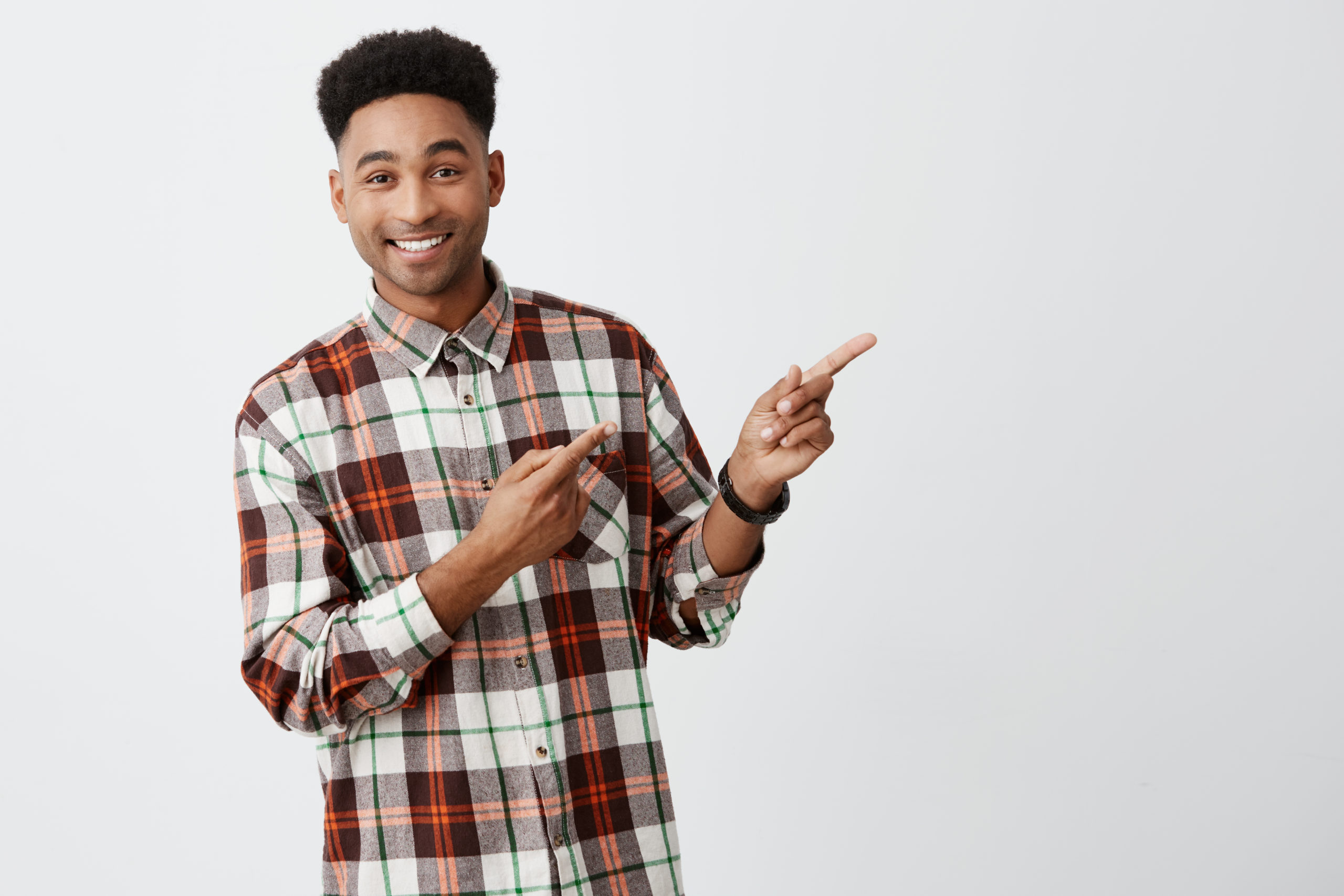 Close up portrait of young good-looking dark-skinned man with stylish dark afro hair in checkered shirt smiling with teeth, pointing aside won white wall with happy and joyful expression.
