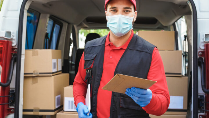 Courier man in front of cargo van delivering package to customer - Focus on left hand